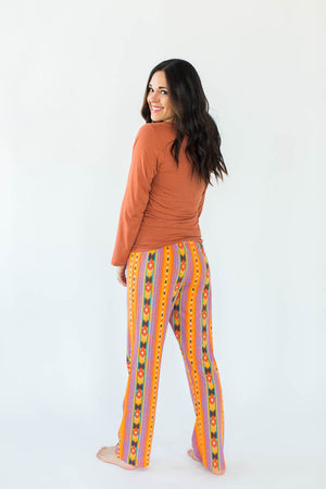 Back View of Southwestern Pajama Set that Features a Burnt Orange Top with A Horse Mustang Print in the Center & Correlating Pants with an Orange, Yellow, & Purple Southwestern Print Design