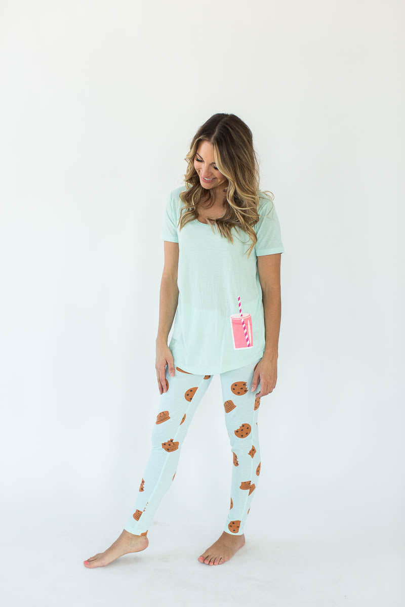 "Milk & Cookies Printed Tee and Legging Pajama Set in Light Turquoise Blue that Features a Scoop-Lined Tee with a Glass of ""Pink Milk"" in the Shirt's Right-Hand Corner with Matching Bottoms that Feature an All-Over Chocolate Chip Cookies Print"