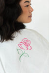 Close-Up View of Rose Applique Short Terry Loop Bathrobe in Bright White with All-Over Colored Rose Appliques that Falls Just Above the Knees & Features an Adjustable Waist Wrap
