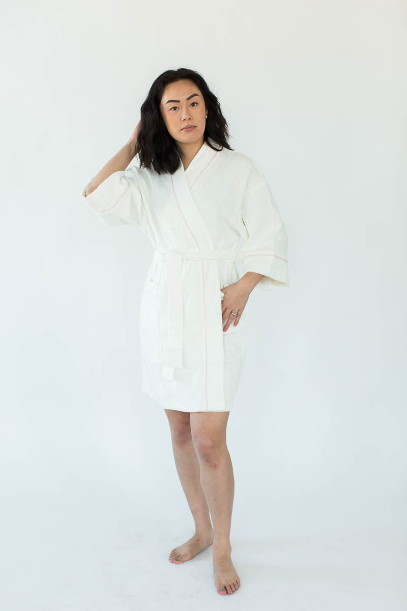 Zero Twist Short Kimono Robe in White with Contrast Piping in Light Pink that Falls Just Above the Knees