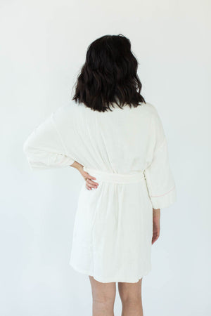 Back View of Zero Twist Short Kimono Robe in White with Contrast Piping in Light Pink that Falls Just Above the Knees