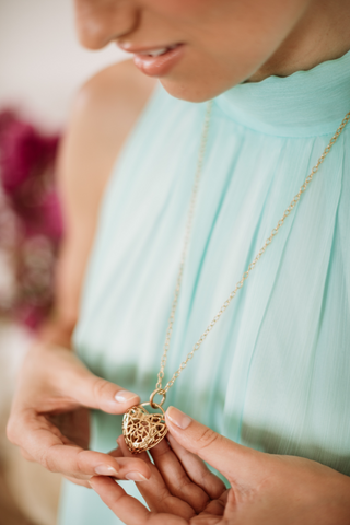 Image of a woman in a blue dress holding a heart shaped locket in her hands