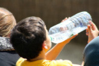 Photo of young boy drinking water from a bottle