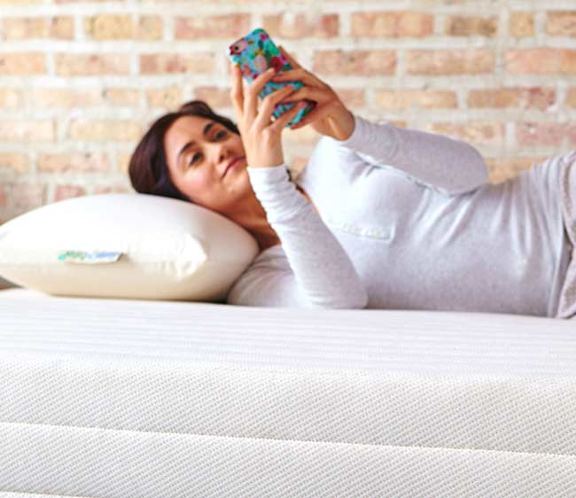 Woman Laying on Pillow with Cell Phone