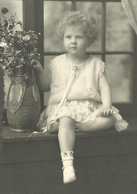 ANTIQUE PHOTO ADORABLE LITTLE GIRL CURLY HAIR POSED ON WINDOW SILL BY FLOWERS - Back from the dead antiques