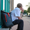 North Point Roll-Top Backpack ACME Made Guy Sitting Next to Bag