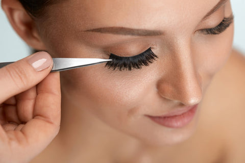 Apply lashes with tweezers