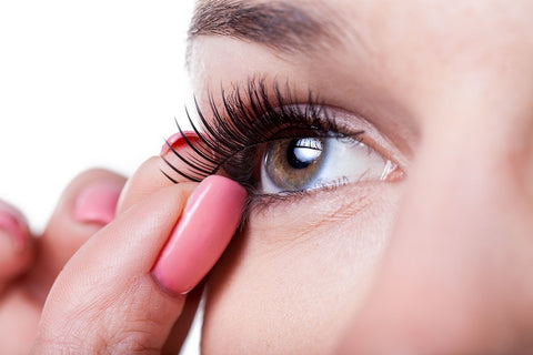woman holding up fake eyelash to her eye