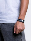 Black wristband with white Barbell Brigade logo on a person's wrist
