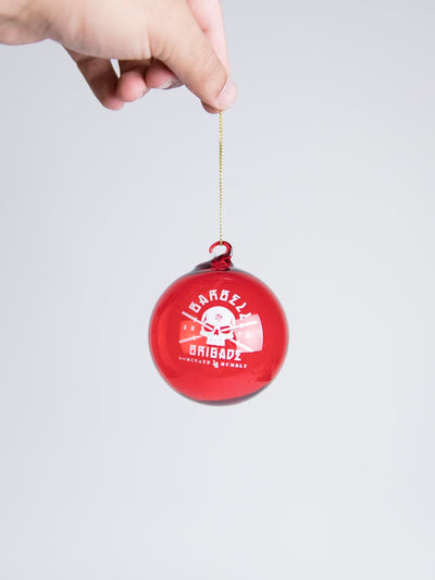 Red glass ornament with Barbell Brigade logo being held up by hand