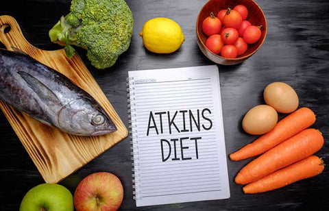 "vegetables and fish on a table with a notepad saying ""Atkins Diet"""