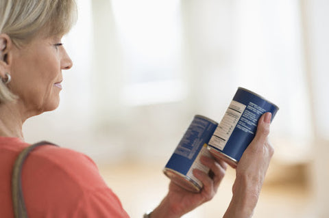 woman reading food labels on two cans