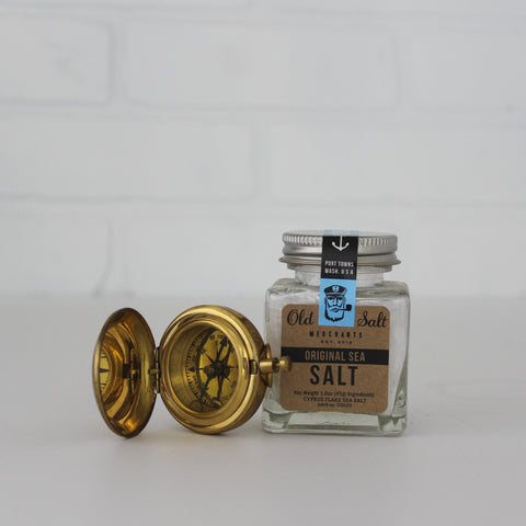 Flaky Kosher Sea Salt Cocktail Rimming Salt, 1.6 oz, next to a brass compass