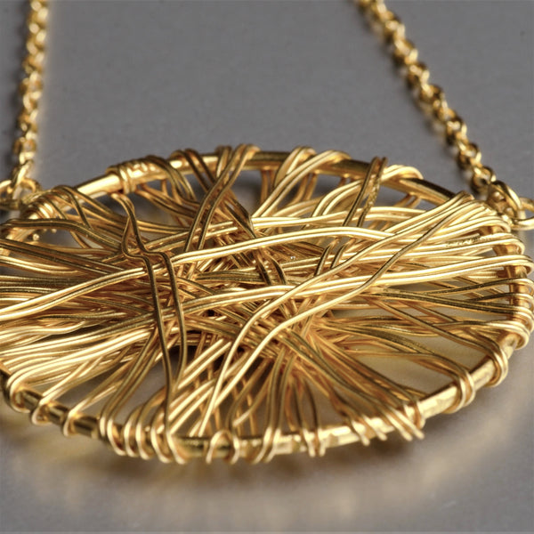 A mysterious yet subtle, dome-shaped lightweight pendant with metal wires wrapped around it. The pendant is 1 3/4 Inch in diameter and held firmly on a 19-inch long necklace.
