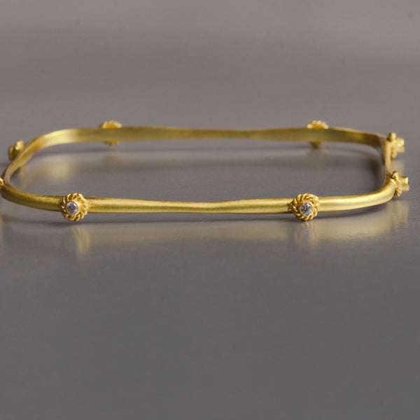 Handmade, asymmetrical, this modern bracelet is augmented with 8 cubic zirconia and artistic bezel set adorn the arm as unique wearable art. It is made with brass and plated efficiently with 18kt gold. The bracelet is 7.5 cm in diame
