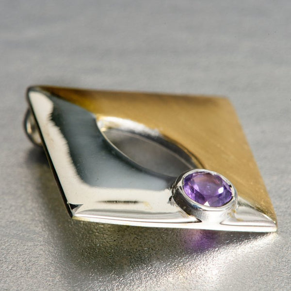 A square-shaped, but when worn it looks more of a diamond-shaped pendant is, two toned-sterling silver on one side and sterling silver with gold plating on the other side. It has a 4mm amethyst gemstone which is embedded with perfection and finesse