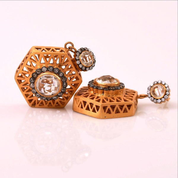 Intricately carved on both sides, these artistic hexagon shaped earrings are mysterious and intriguing. Bold cubic zirconia in the middle reflects the luminious and opulent characteristic with gratification. 18 Kt Gold plating on base metal, it flaunts elegance and sophistication.