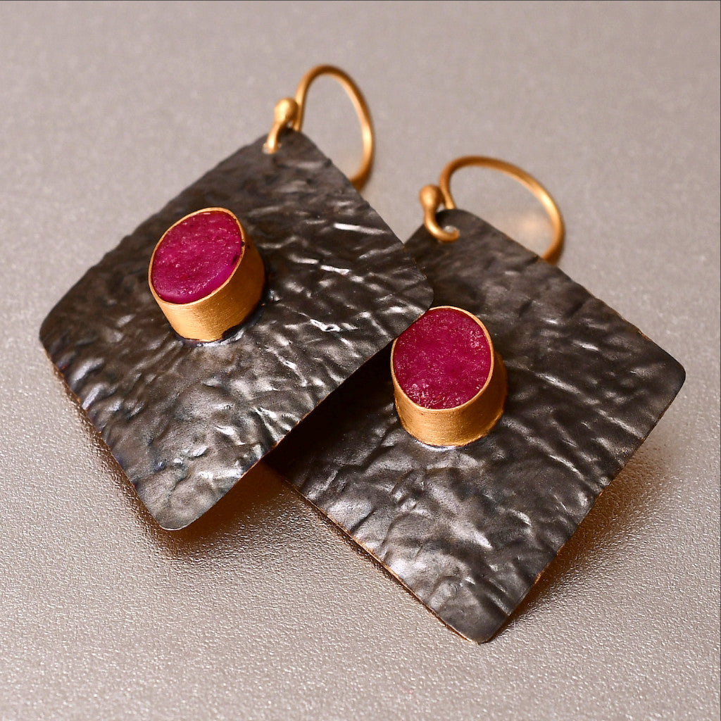 Captivating, lightweight earrings with a hand hammered texture is loved for its verstallity. Dress up or dress down. The earrings are 4.5 cm long and 3 cm wide. It has a 1 cm dyed ruby with a druzy effect which is unique and eye-catching.