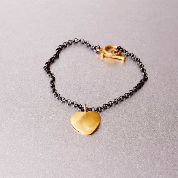 This adorable and charming, black rhodium plated delicate bracelet with a sterling silver base, showcase a flattering and dainty 'heart-shaped' charm.
