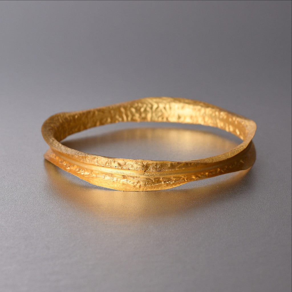 Some jewelry pieces need no description, literally! Stack them together OR wear them individually. Lightweight bangle/bracelet with 18kt gold plating. Showcasing an artistic and mysterious vibe, these bangles are glamorous, charismatic and has a playful characteristic to it. A lightest sheet of metal is molded and hammered to give it a unique earthy rustic texture.
