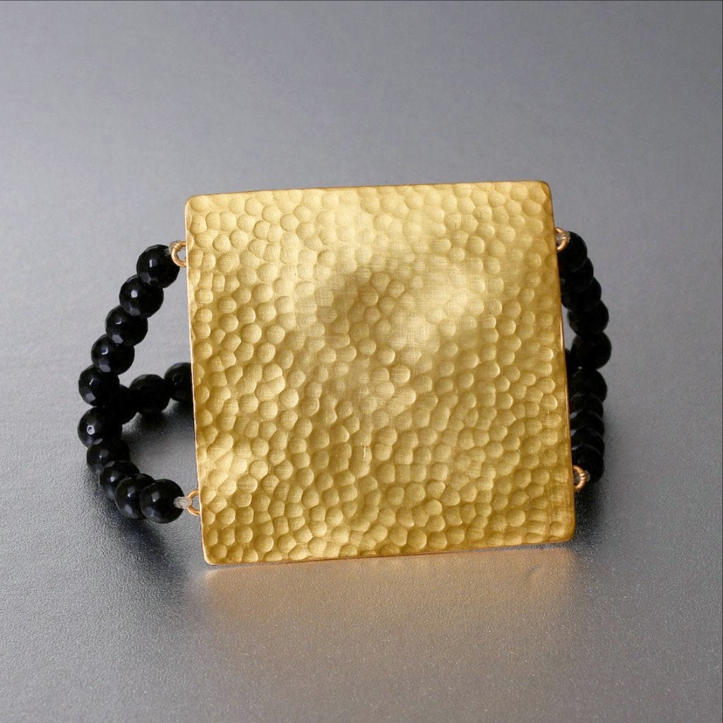 A little outside the box, one may say. A somewhat chunky design that incorporates a luxe boho appeal to an earthy yoga culture. A stretchable bracelet to make the bracelet sit in the manner you want. The bracelet is gold plated on brass with 2 rows of black onyx beads.