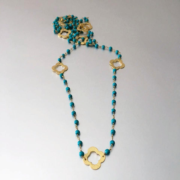 "An everyday essential is reimagined with the 'Clover Necklace'. Featuring tiny, lightweight turquoise beads and adorable gold plated clover charms hung graciously all around the necklace. The common saying, ""looks can be deceiving"" is appropriate to use for this necklace. Lightweight, delicate yet sturdy and durable and surely creating the statement look."