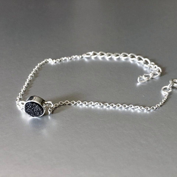 An adjustable, dainty, lightweight, sterling silver bracelet with stunning sparkling black druzy adds an artful addition to your everyday look.