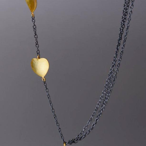 A unique design where one side of the necklace holds cute little, gold plated 'heart' charms and on the other side is where 3 plain chains are put together.  The sterling silver withlack rhodium plated necklace then holds another heart charm as a pendant.