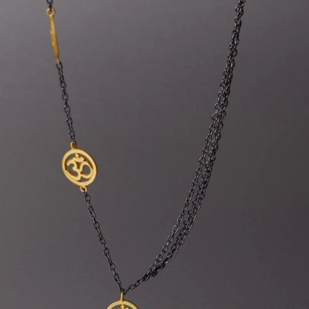 A spiritually inclined design where one side of the necklace holds cute little, gold plated 'OM' charms and on the other side are 3 plain chains. The necklace then holds yet another sleek, handcrafted 'OM' charm as a pendant. The necklace is a sterling silver base with black rhodium plating.