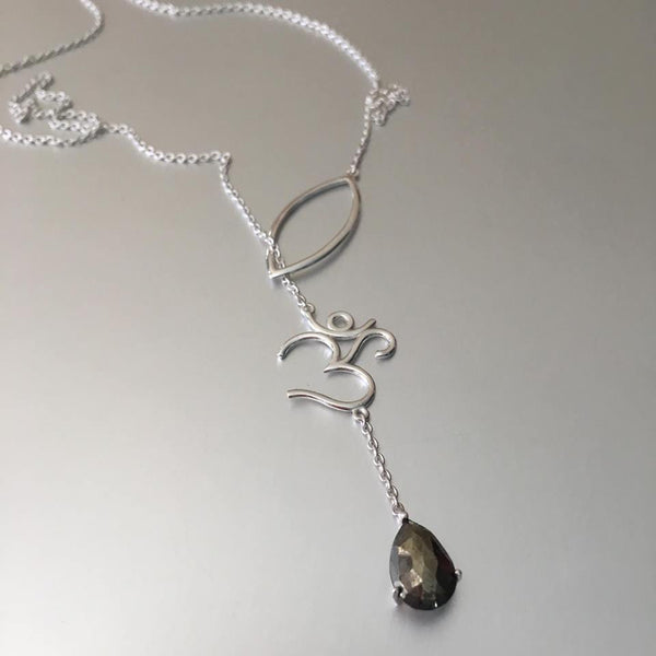 "The most unusual design from the new collection: The lariat necklace. What better choice of pendant and charm than an ""OM"" with a smoky quartz gemstone. The delicate sterling silver chain goes through gracefully via the petal thereby exuding elegance and perfection of the OM"