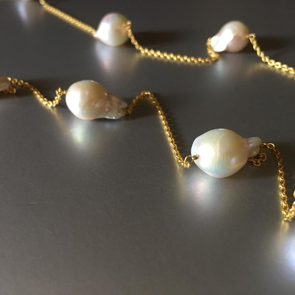 A beautiful twist on a classy pearl necklace, the weight is beautifully balanced by the equal amount of pearls on each side.