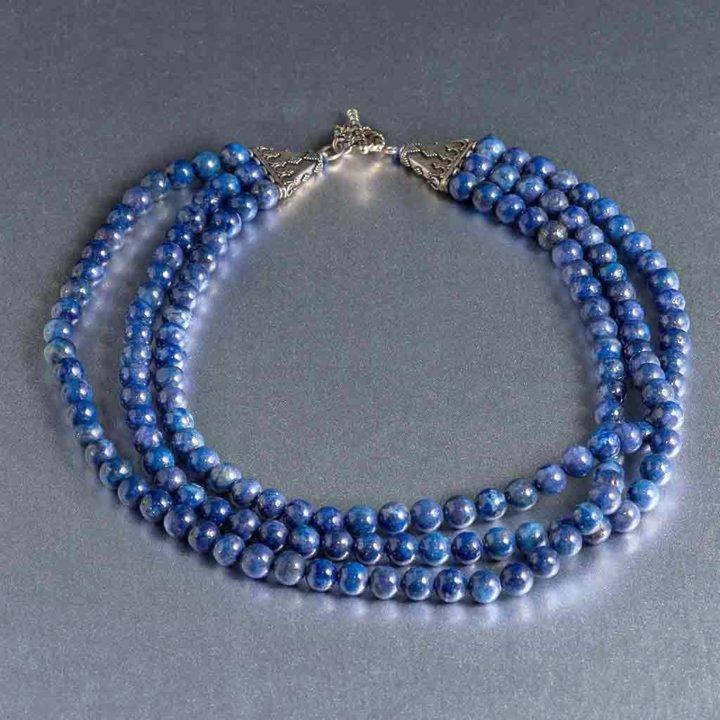 "This gorgeous multi-strand lapis lazuli necklace simply exudes elegance and a classy appeal. It holds deep blue 8 mm lapis lazuli gemstones with beautiful variations of color and rich striations of pyrite running through it is and is strung together with a sterling silver 3 prong sturdy toggle clasp. The necklace is 17 ½"" at its shortest strand to 20"" at its longest hanging last layer."