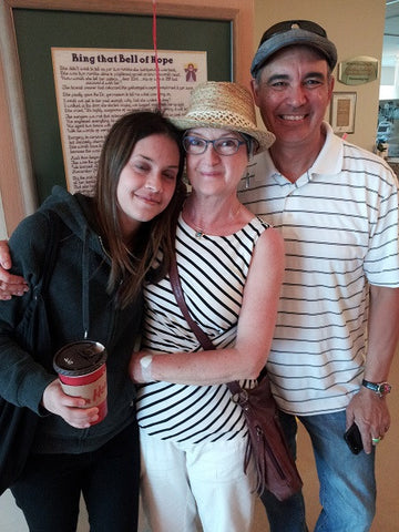 Claire, with her duaghter and husband, ringing the Bell of Hope after her last chemo treatment