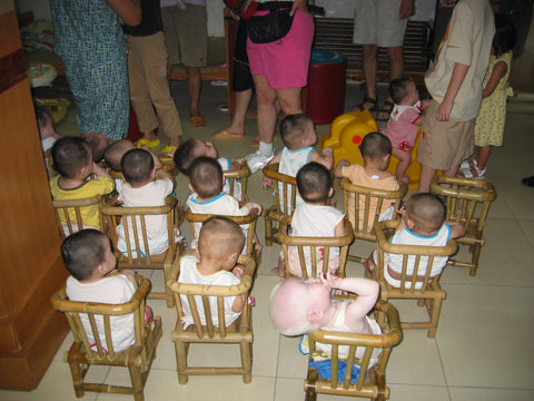 Babies in the little wooden chairs at the orphanage