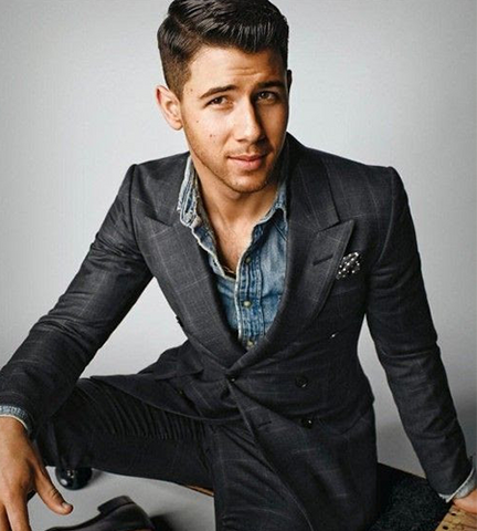 Nick Jonas in a suit paired with a denim shirt