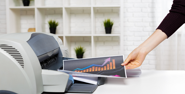 Image of a printer printing a colored graph and person grabbing the paper
