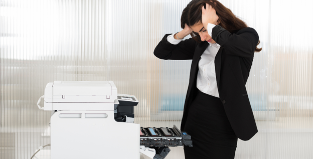 woman standing over printer with frustrated expression
