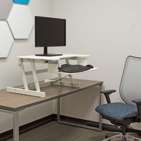 Lorell sit-to-stand monitor riser in white in office setting