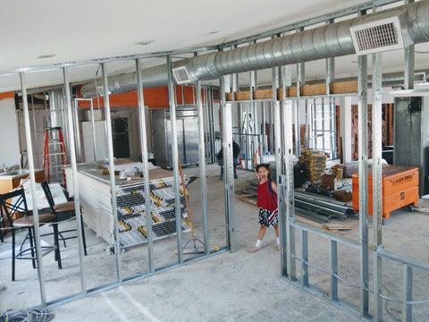 Walls going up with the help of the co-owner's daughter during the renovations of Trianon Coffee in summer 2018