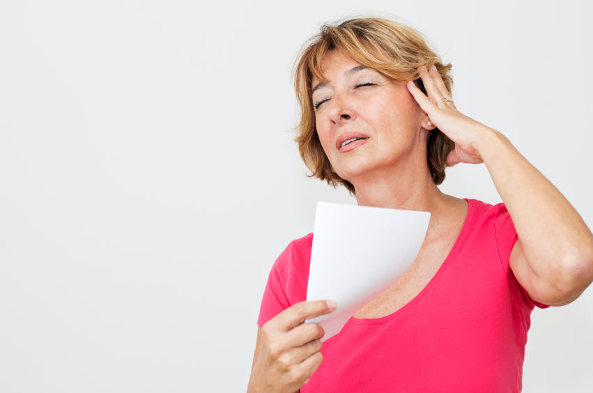 woman with hot flash fanning with paper