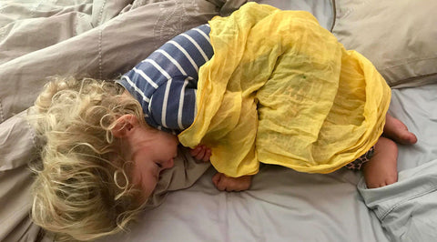 small child sleeping with yellow wrapmecool