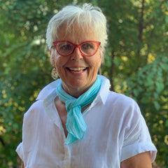 woman in white blouse with light blue neck scarf
