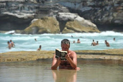 man sitting and reading in pool of water to stay cool