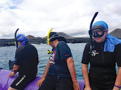 3 men on inflatable boar with snorkel gear