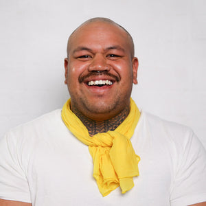 male with white T-shirt and yellow daffodil neck scarf