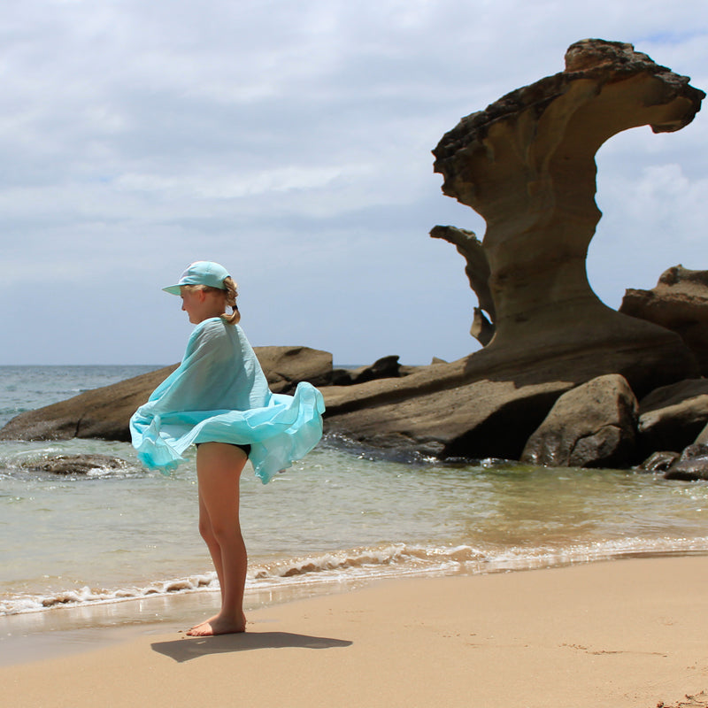young girl on beach with aqua wrap