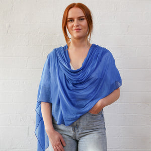 female with cornflower blue wrap and faded blue jeans
