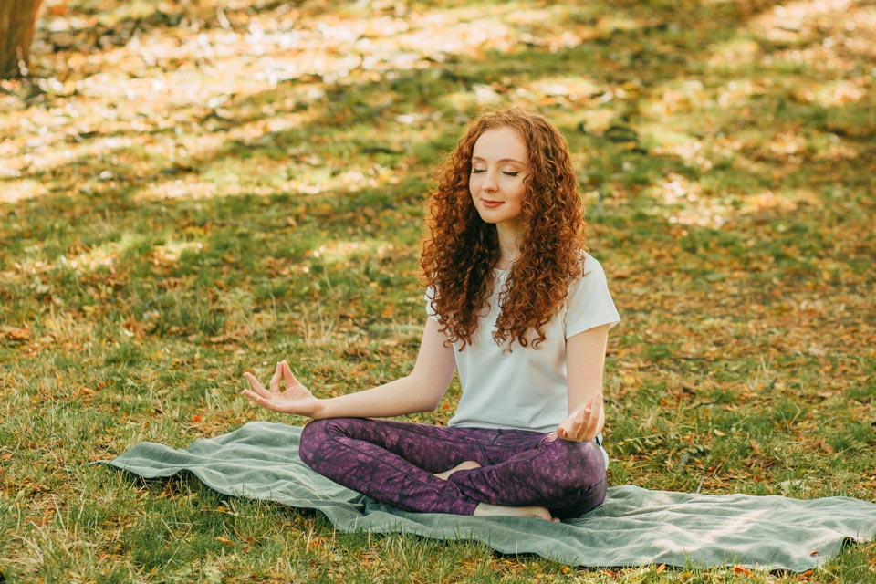 Young woman practicing mindfulness with yoga and meditation