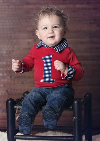 baby boy with red first birthday shirt navy gingham and jeans