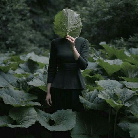 girl covers her face with a leaf